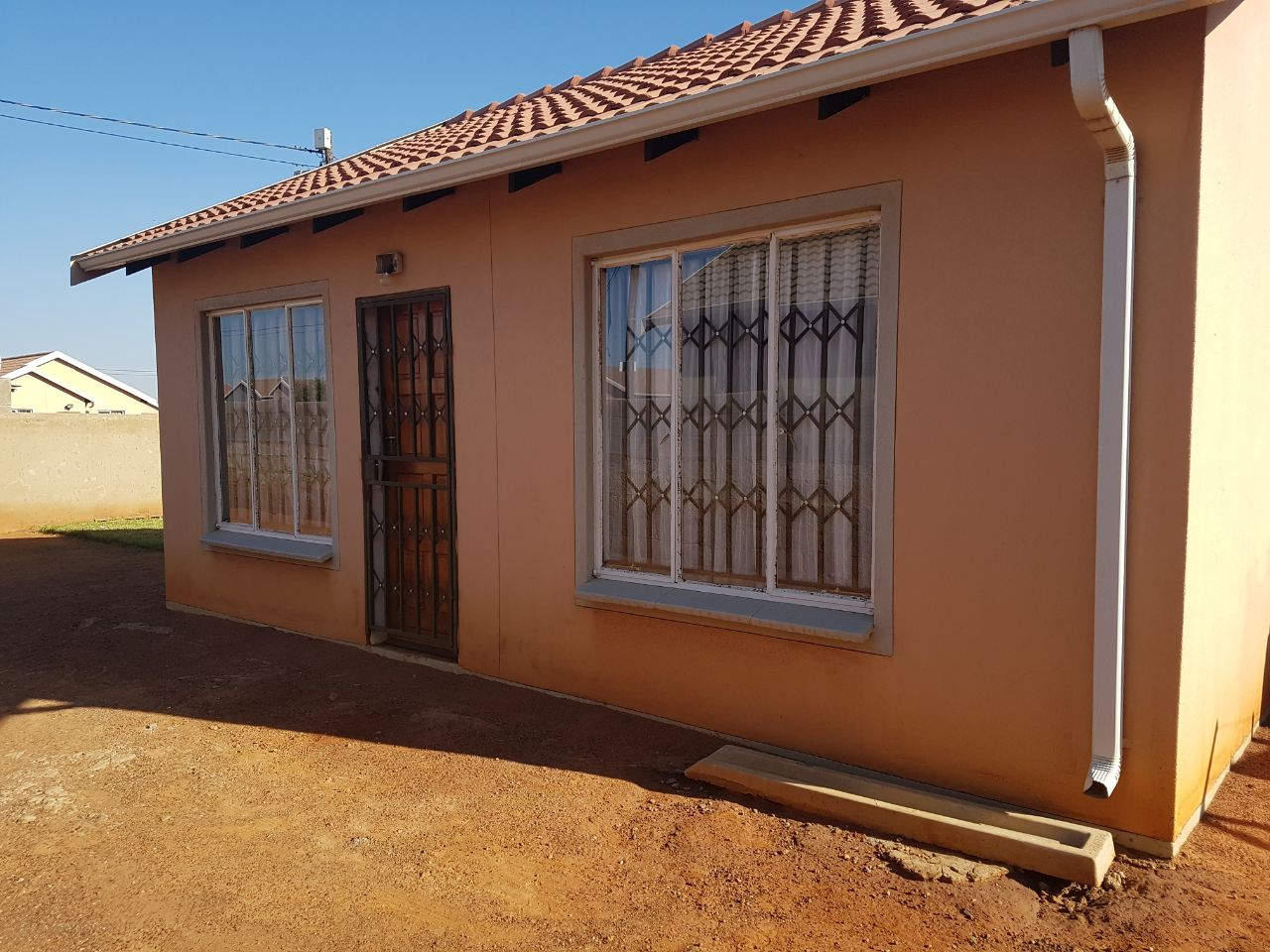 Secure 2 Bedroom House with an open plan kitchen and lounge,bathroom with a toilet.Secure high walls with a secure locking gate for rental at Protea Glen Ext 27,23948 Mandarine Crescent