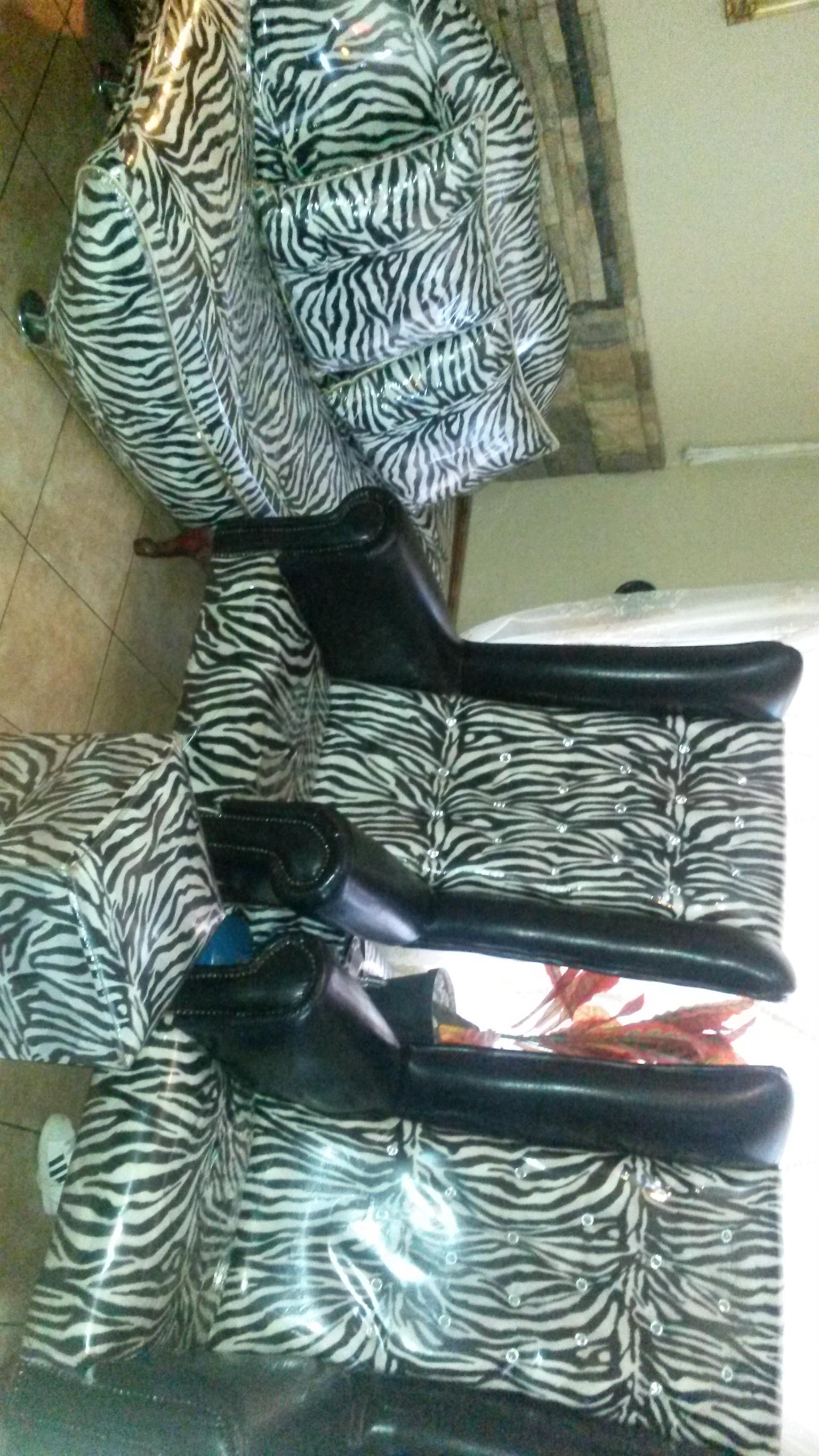 Zebra theme wedding chairs, a side couch with two pillows and a foot stool